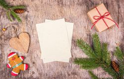 Weihnachtsdekorationen mit Tannenbaum, Geschenkbox, Lebkuchen auf hölzernem Brett Lebkuchen-Mann und hölzernes Herz Stockbild