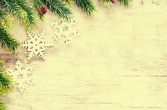 Weihnachtsdekorationen mit Tannenbaumast und -schneeflocken Stockfotos
