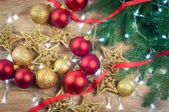Weihnachtsdekorationen mit Tannenzweigen auf hölzernem Hintergrund, Bälle und Sterne, Gold und Rot lizenzfreie stockfotografie