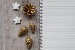 Weihnachtsdekorationen, Sankt-` s weißer Stiefel, goldene Tannenzapfen, Schneeflocken und ein offenes leeres Notizbuch, hölzerner stockfoto
