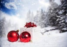 Weihnachtsdekorationen und -Geschenkbox im Schnee Stockfotos