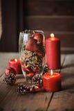 Weihnachtsdekorationen und Kiefernkegel im Glasvase Stockbild