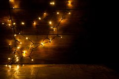 Weihnachtsdekorationen und -lichter auf hölzernem Hintergrund Stockfotografie