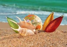 Weihnachtsdekorationen und -Seashell auf einem Strand stockfoto