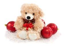 Weihnachtsdekorationen und -Teddybär, die ein Geschenk anhalten Stockfoto