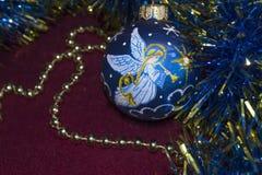 Weihnachtsdekorationen Weihnachten und neues Jahr, Perlen, Lametta, blauer Ball mit einem Engel auf einem Burgunder-Hintergrund Lizenzfreies Stockfoto