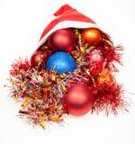 Weihnachtsdekorationen werden heraus von rotem Sankt-Hut verschüttet Stockfotos