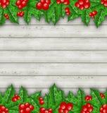 Weihnachtsdekorations-Stechpalmenbeere verzweigt sich auf hölzernen Hintergrund Stockfoto
