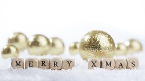 Weihnachtsdekorationsbälle und Text der frohen Weihnachten Stockfotografie