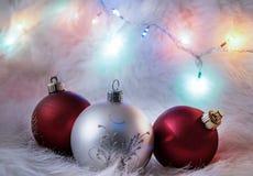 Weihnachtsdekorationsball und buntes Licht auf Pelzhintergrund Lizenzfreie Stockfotografie