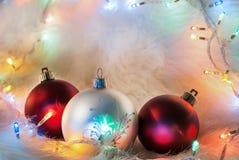 Weihnachtsdekorationsball und buntes Licht auf Pelzhintergrund und Raum für Design Stockbild