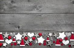 Weihnachtsdekorationsgrenze in weißem und in Rotem auf grauer hölzerner Rückseite Stockbild