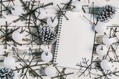 Weihnachtsdekorationshintergrund, obenliegende Ansicht des Notizbuches und handgemachte Weihnachtsverzierungen auf rustikaler höl Stockfotografie