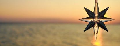 Weihnachtsdekorationsstern auf dem Hintergrund des Sonnenuntergangs auf dem Meer fahne lizenzfreies stockfoto