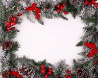 Weihnachtsdekorative Grenze mit Kiefernkegeln und Stechpalmenbeeren Stockbilder