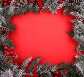 Weihnachtsdekorative Grenze mit Kiefernkegeln und Stechpalmenbeeren Stockfotografie