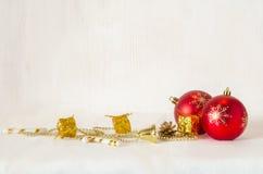 Weihnachtsdekorative rote Bälle auf Schnee mit hölzernen Planken als Hintergrund Lizenzfreies Stockbild