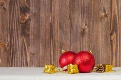 Weihnachtsdekorative rote Bälle auf Schnee mit hölzernen Planken als Hintergrund Lizenzfreie Stockfotografie