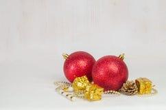 Weihnachtsdekorative rote Bälle auf Schnee mit hölzernen Planken als Hintergrund Stockbilder