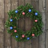 Weihnachtsdekorativer Kranz mit Bällen auf Holz Lizenzfreie Stockfotografie