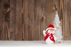 Weihnachtsdekorativer Schneemann auf dem dunklen hölzernen Hintergrund Lizenzfreie Stockfotos