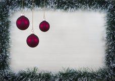 Weihnachtsdesignweihnachtskarte eingesäumt mit Kiefernnadeln und roten Ballonen mit Platz für Text Lizenzfreie Stockfotos