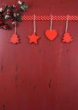 Weihnachtsdunkelrote Weinlese bereitete hölzernen Hintergrund mit hängenden hölzernen Verzierungen auf Stockfoto