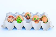 Weihnachtsei mit den gezeichneten Gesichtern vereinbarte im Karton Lizenzfreie Stockbilder
