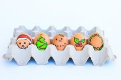 Weihnachtsei mit den gezeichneten Gesichtern vereinbarte im Karton Stockfotos