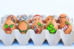 Weihnachtsei mit den gezeichneten Gesichtern vereinbarte im Karton Stockbilder
