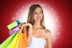 Weihnachtseinkaufsfrau mit bunten Taschen auf rotem Hintergrund Stockfoto