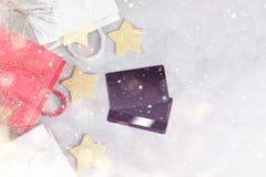 Weihnachtseinkaufshintergrund: rote und weiße Papiertüten und Kreditkarten unter Schnee Lizenzfreie Stockbilder