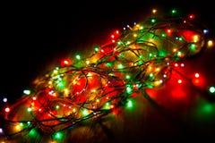 Weihnachtselektrische Girlande auf einem dunklen Hintergrund lizenzfreie stockfotos