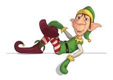 Weihnachtself, der auf einen Rand legt Stockbild