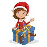 Weihnachtselfe, die auf Geschenk sitzt Lizenzfreie Stockfotos