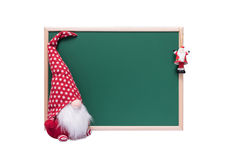 Weihnachtselfe und -Santa Claus Ornament Beside ein leeres grünes Cha Lizenzfreie Stockfotos