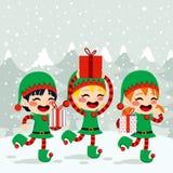 Weihnachtselfen, die Geschenke tragen Lizenzfreie Stockfotos
