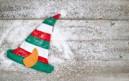 Weihnachtselfen-Strumpf auf rustikalem Holz mit Schnee Lizenzfreie Stockbilder