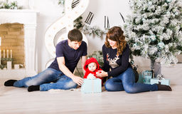 Weihnachtsfamilie mit Babyöffnungsgeschenken glücklich Lizenzfreie Stockfotos