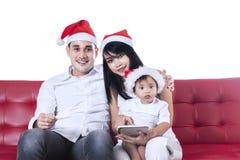 Weihnachtsfamilie unter Verwendung einer Tablette Stockfotos