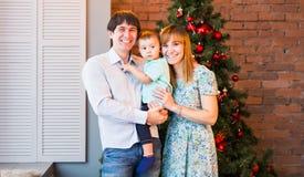 Weihnachtsfamilien-Porträt im Hauptfeiertags-Wohnzimmer, Haus, das durch Weihnachtsbaum verziert stockfotografie