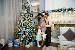 Weihnachtsfamilienstellung nahe dem Weihnachtsbaum Wohnzimmer verziert durch Weihnachtsbaum und anwesende Geschenkbox lizenzfreie stockbilder