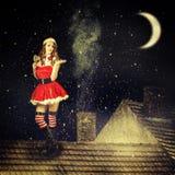 Weihnachtsfeenhafte Frau im rotem Kleid und in Sankt-Hut Stockfotos
