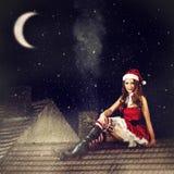 Weihnachtsfeenhafte Frau im rotem Kleid und in Sankt-Hut Stockbild