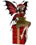 Weihnachtsfeenhaftes Elfen-Mädchen, das auf einem Geschenk sitzt Lizenzfreies Stockfoto