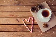 Weihnachtsfeiertags-Teeschale auf alten Büchern mit Liebe formte Süßigkeit auf Holztisch mit Kopienraum Stockbild