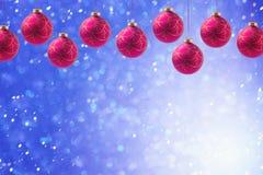 Weihnachtsfeiertagsbälle, die über blauem boke Hintergrund mit Kopienraum hängen Lizenzfreie Stockfotos