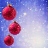Weihnachtsfeiertagsbälle, die über blauem bokeh Hintergrund mit Kopienraum hängen Stockfotografie