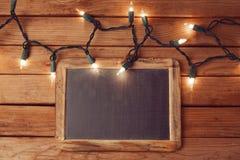Weihnachtsfeiertagshintergrund mit leerer Tafel und Weihnachtslichtern Stockbild