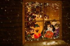 Weihnachtsfenster, Familie, die Weihnachtsfeiertag innerhalb des Hauses feiert stockbilder